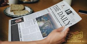 موکاپ روزنامه یا مجله روی میز کار و دست خواننده