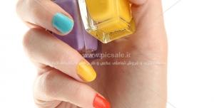 عکس با کیفیت لاک های رنگی با رنگ های زرد و بنفش بر فراز دست