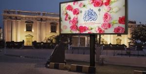 موکاپ بنر تبلیغاتی لایه باز در حاشیه خیابان سنگ فرش و مقابل عمارتی زیبا در شب
