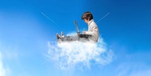 عکس با کیفیت کودک پسر در حال کار با لب تاپ نشسته بر روی ابرها و در آسمان