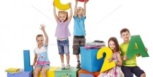 عکس با کیفیت کودکان نشسته بر روی باکس با نمادهای حروف و اعداد زبان انگلیسی رنگارنگ