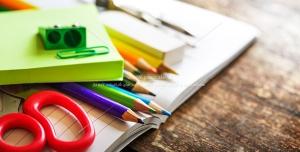عکس با کیفیت مدادهای رنگی و لوازم التحریر و دفتر بر روی میز چوبی