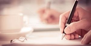 عکس با کیفیت مطالعه کتاب در کنار عینک و روان نویسی در دست با فنجان قهوه