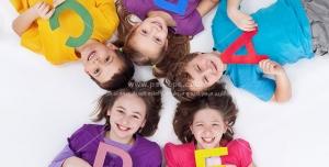 عکس با کیفیت حلقه کودکان شاد با حروف الفبای انگلیسی رنگی در دست