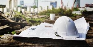 عکس با کیفیت برگه های طرح ها و نقشه های معماری با کلاه سفید ایمنی بر روی میز با زمینه شهر