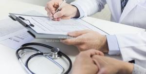 عکس با کیفیت پزشک با لباس سفید پزشکی و استتوسکوپ در حال ثبت نتایج معاینه