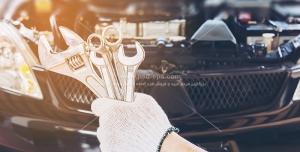 عکس با کیفیت ابزارآلات تعمیرات در دستان تعمیرکار ماشین با زمینه خودرو
