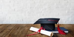 عکس با کیفیت کلاه فارغ التحصیلی و گواهینامه پایان تحصیلات بر روی میز