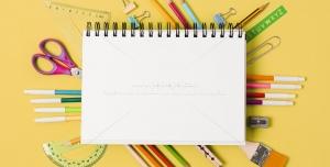عکس با کیفیت لوازم التحریر مختلف از جمله مداد رنگی ، ماژیک ، نقاله ، گیره ، گونیا ، قلم مو و ... در کنار دفتر نقاشی فنری