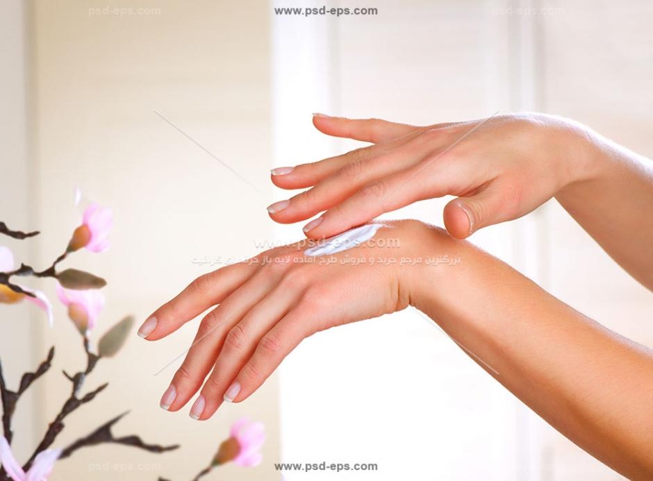 عکس با کیفیت ماساژ دست با کرم پوست دست و بدن در کنار گل های بهاری