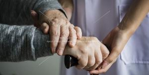 عکس با کیفیت پرستاری از سالمندان ، دستان حمایت گر پرستار در حال کمک به پیرزن