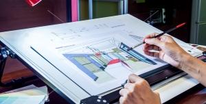عکس با کیفیت مهندس معمار در حال طراحی و نقشه کشی بر روی میز نقشه کشی معماری