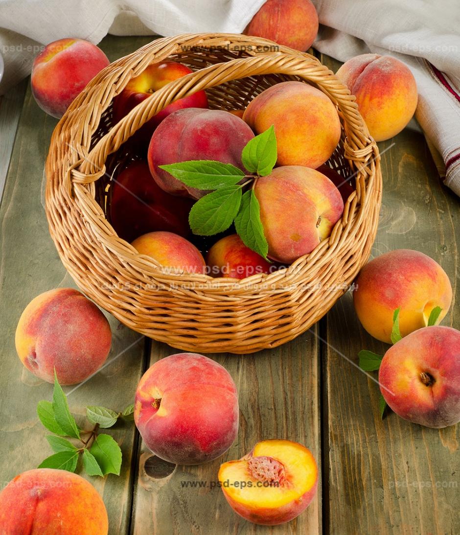 عکس با کیفیت میوه های هلو درون سبد حصیری و روی میز چوبی