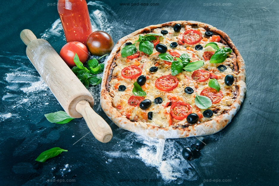 عکس با کیفیت پیتزا آماده بر روی میز در کنار سس گوجه و ریحان و وردنه آشپزی