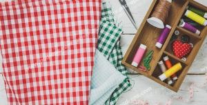 عکس با کیفیت جعبه وسایل و ابزار خیاطی از جمله قیچی ، نخ و پارچه های چهارخانه قرمز و سبز و سفید رنگ بر روی میز چوبی ویژه استفاده در امور تبلیغاتی و تجاری طراحی کاتالوگ ، بروشور و تراکت با موضوع خیاطی ، تولیدی لباس ، آموزش خیاطی یا موسسات فنی و حرفه ای آموزش مقدماتی تا حرفه ای و لباس شب و لباس عروس