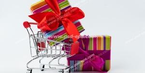 عکس با کیفیت جعبه های هدیه یا کادوی رنگارنگ با روبان بزرگ قرمز رنگ کنار و درون سبد خرید از مراکز خرید ویژه استفاده در امور تبلیغاتی و تجاری طراحی کاتالوگ ، بروشور و تراکت با موضوع خرید کادو و هدیه ، مراکز خرید ، هایپرمارکت و فروشگاه های بزرگ
