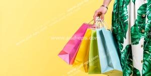 عکس با کیفیت پاکت کاغذی یا ساک دستی های خرید در دستان مشتری خانم ویژه استفاده در امور تبلیغاتی و تجاری طراحی کاتالوگ ، بروشور و تراکت با موضوع خرید و فروش از فروشگاه لباس ، کیف و کفش بانوان