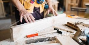 عکس با کیفیت نجار در حال کار بر روی چوب با چکش ، کاتر ، نقاله ، رنده ، کولیس و گیره بر روی چوب ویژه استفاده در امور تبلیغاتی و تجاری طراحی کاتالوگ ، بروشور و تراکت با موضوع نجاری ، صنایع چوب و ساخت میز ، مبل و صندلی