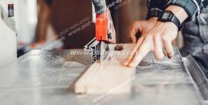 عکس با کیفیت نجار در حال کار با اره عمود بر در حال برش چوب ویژه استفاده در امور تبلیغاتی و تجاری طراحی کاتالوگ ، بروشور و تراکت با موضوع نجاری ، صنایع چوب و ساخت میز ، مبل و صندلی