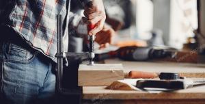 عکس با کیفیت نجار در حال کار با پیچ دستی بر روی چوب ویژه استفاده در امور تبلیغاتی و تجاری طراحی کاتالوگ ، بروشور و تراکت با موضوع نجاری ، صنایع چوب و ساخت میز ، مبل و صندلی