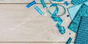 عکس با کیفیت پارچه ، متر ، نخ ها و دکمه های آبی و ابزار خیاطی روی میز چوبی