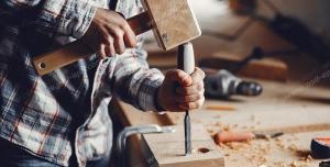عکس با کیفیت نجار در حال کار با چکش و مغار تخت و چوب ویژه استفاده در امور تبلیغاتی و تجاری طراحی کاتالوگ ، بروشور و تراکت با موضوع نجاری ، صنایع چوب و ساخت میز ، مبل و صندلی
