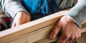 عکس با کیفیت نجار با چوب برش خورده در دست ویژه استفاده در امور تبلیغاتی و تجاری طراحی کاتالوگ ، بروشور و تراکت با موضوع نجاری ، صنایع چوب و ساخت میز ، مبل و صندلی