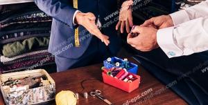 عکس با کیفیت خیاط آقایان در حال سفارش گیری از مشتری در کنار میز و ابزار خیاطی و طاقه های پارچه