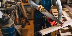 عکس با کیفیت نجار با لباس کار در حال برش چوب با اره دستی ویژه استفاده در امور تبلیغاتی و تجاری طراحی کاتالوگ ، بروشور و تراکت با موضوع نجاری ، صنایع چوب و ساخت میز ، مبل و صندلی