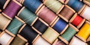 عکس با کیفیت قرقره های چوبی نخ چیده شده در کنار هم با رنگ های مختلف تیره و روشن