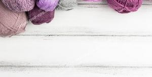 عکس با کیفیت نمای نزدیک از نخ های بافتنی بنفش رنگ برای قلاب بافی و بافت دومیل بر روی میز