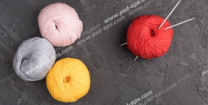 عکس با کیفیت نخ های بافتنی با رنگ های قرمز و صورتی و توسی و زرد با دو میل بافتنی