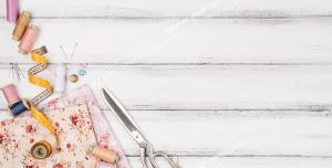 عکس با کیفیت پارچه گل دار در کنار ابزار خیاطی قیچی ، متر ، سوزن و نخ های رنگارنگ بر روی میز چوبی