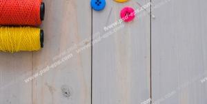 عکس با کیفیت قرقره های نخ های رنگی در کنار دکمه های رنگی و سوزن های چیده شده روی میز چوبی