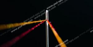 عکس با کیفیت نمای نزدیک از نخ و سوزن با دو نخ نارنجی و قرمز و زمینه مشکی رنگ