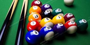 عکس با کیفیت توپ های رنگارنگ بیلیارد و چیده شده در کنار هم و چوب های بیلیارد بر روی میز