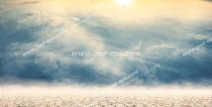 عکس با کیفیت بیابان خشک و زمین ترک خورده در آسمان نیمه ابری و با تلالو نور نارنجی خورشید