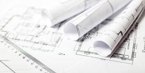 عکس با کیفیت نقشه های معماری و طراحی ساختمان باز شده روی میز همراه با نقشه های لوله شده