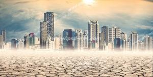 عکس با کیفیت شهر مدرن در بیابانی خشک و زمین ترک خورده با آسمان نیمه ابری و تلالو نور خورشید