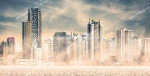 عکس با کیفیت نمایی از شهر مدرن و برج های بلند در بیابانی خشک و زمینی ترک خورده