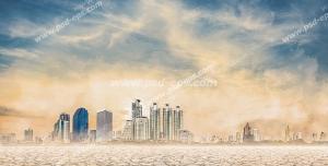عکس با کیفیت نمای دور از شهر مدرن و برج های بلند در بیابانی خشک و زمینی ترک خورده