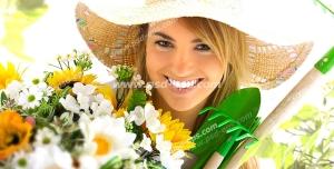 عکس با کیفیت چهره و فون زیبای بانوی باغبان به همراه لوازم باغبانی و دسته گلی بزرگ در دست با زمینه درختان باغ