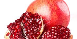 عکس با کیفیت انار سالم و تکه های انار پوست شده و سرخ بر روی زمینه سفید