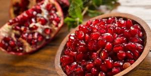 عکس با کیفیت دانه های انار درون پیاله چوبی و تکه های انار و شاخه کوچک درخت بر روی میز