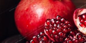عکس با کیفیت انار سالم و تکه های پوست کنده و جدا شده انار سرخ درون بشقاب