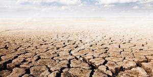عکس با کیفیت بیابان خشک با زمین ترک خورده با آسمان آبی و ابری