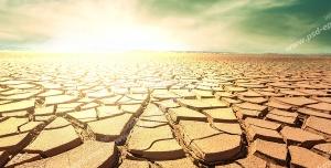 عکس با کیفیت زمین ترک خورده بیابان و خورشید در حال غروب در آسمان