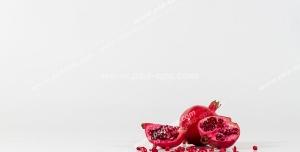 عکس با کیفیت نمای دور از انارهای سالم و تکه شده در کنار دانه های انار بر روی زمینه سفید