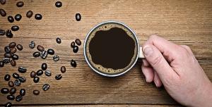 عکس با کیفیت فنجان قهوه بر روی میز و در دست مهمان در کنار دانه های قهوه