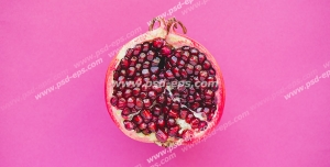 عکس با کیفیت انار نیمه شده با دانه های سرخ و تازه بر روی زمینه صورتی رنگ
